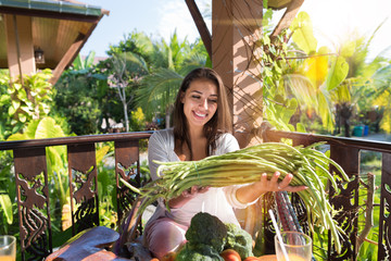 Portrait Of Beautiful Woman Holding Asparagus Happy Smile Sitting At Table On Summer Terrace With Tropical Forest Background Organic Food And Nutrition Concept