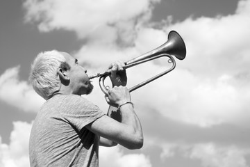 Man playing trumpet on sky background