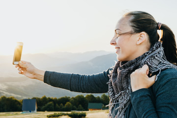 Smiling Woman traveler takes selfie on the phone mountains at dawn