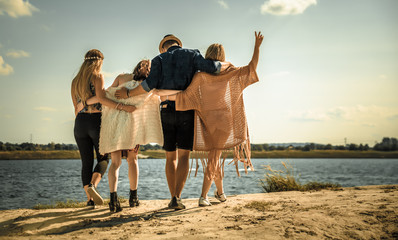 Group of happy friends walking on beach, fashion styled