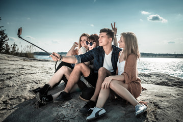 Group of friends taking self portrait with selfie stick, having fun at beach