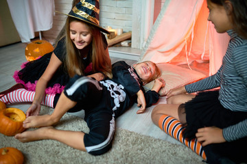 Playful cute little witch tickling foot of boy dressed as skeleton lying on floor, smiling friend observing them at Halloween party
