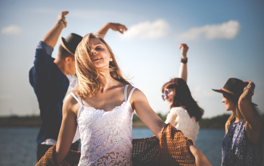 Group of friends dancing and celebrating on beach, party outdoor