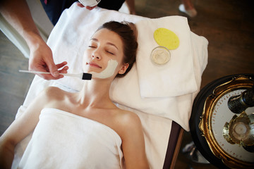Top view portrait of beautiful young woman in SPA, lying on massage table enjoying face masks and beauty treatments