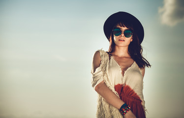 Styled hippie girl on sky background, boho fashion
