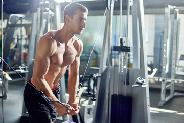 Handsome young bodybuilder with bare muscular torso exercising on cable crossover machine during intensive training in spacious gym
