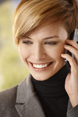Closeup of happy young woman talking on mobile
