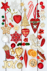 Christmas bauble decorations with gold joy sign, holly, mistletoe, gingerbread biscuits, dried orange fruit and mince pie on rustic white wood background.