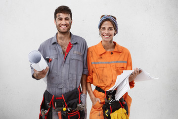 Joyful handyman and female architect collaborate together, wear working clothes, hold sketches with new construction plan, smile broadly, stand next to each other over white blank studio wall Wall mural