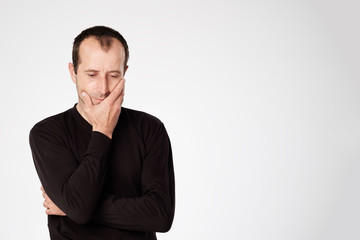 Caucasian man in black shirt looking down with skeptical emotion on face.