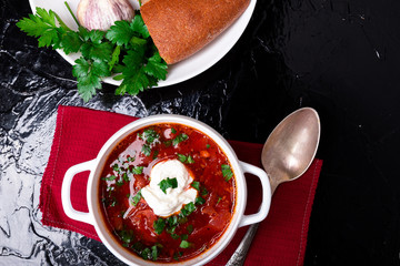 Ukrainian traditional borsch. Russian vegetarian red soup  in white bowl on black background. Top view.  Borscht, borshch with beet.