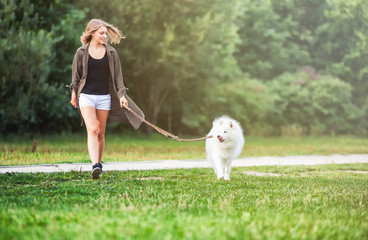Girl walking dog at the park, samoyed