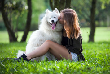Pretty girl hugging and kissing her dog at the park, samoyed