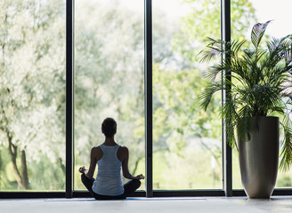 Woman meditating in class. Girl practicing yoga
