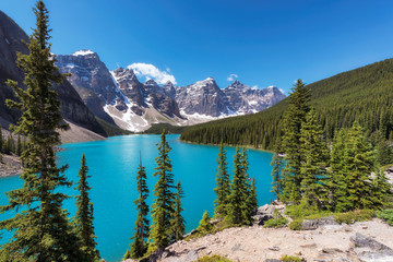 Beautiful turquoise waters of the Moraine lake with snow-covered peaks above it in Banff National Park, Canada.