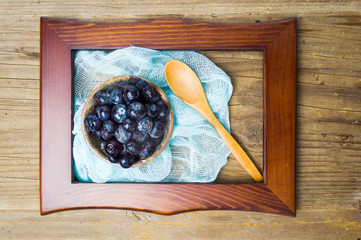 Blueberry fruit in a bowl in a wooden frame