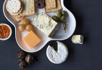 Cheese plate served with various crackers, jam, figs, caper berries and pickled onions. Top view photo with space for text