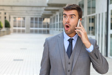 Businessman getting shocking news on the phone