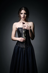 Portrait of beautiful goth girl holding withered rose in hands