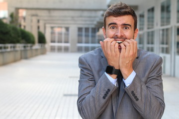 Anxious businessman biting his nails isolated