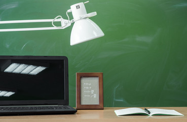 Teacher, student desk table. Education background. Education concept. Laptop with blank screen, copybook, pen, lamp and photo frame on the table with blackboard background.