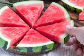Woman hand take slice of fresh seedless watermelon cut into triangle shape laying on a wooden plate, horizontal
