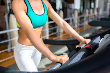 Slim young woman in activewear running on treadmill in sport club