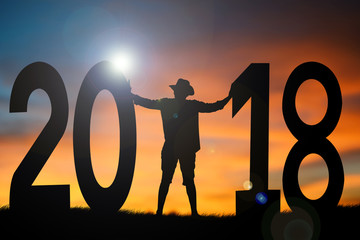 Silhouette man standing with 2018 word at sky sunset, concept Happy New year