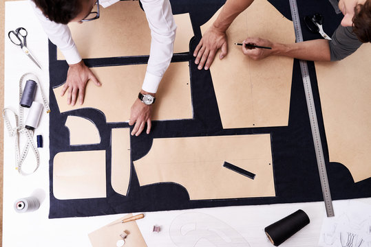 High angle view of concentrated young tailors using sewing patterns while working on creation of custom-made male jacket