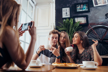 Group of cheerful young people posing in a cafe drinking coffee making faces while their friend photographing them with mobile phone