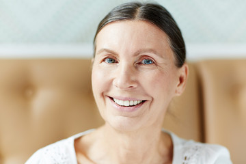 Portrait of happy mature woman with toothy smile looking at camera