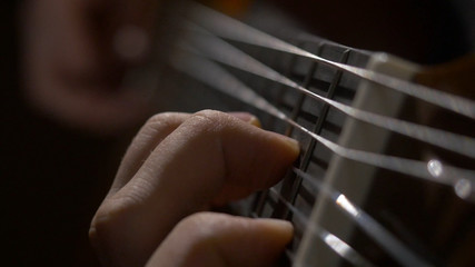 Close up of guitarist hand playing acoustic guitar. Close up shot of a man with his fingers on the frets of a guitar playing