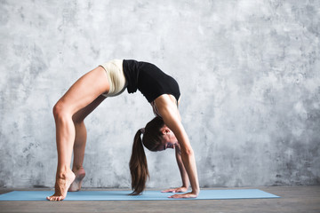 Beautiful young woman workout at home indoors, doing yoga or pilates exercise on blue mat full length.