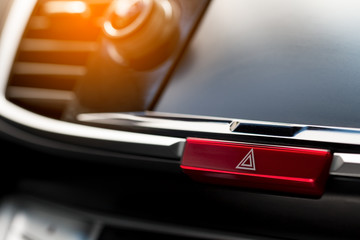 close-up of car dashboard, hazard flasher switch or emergency light button in modern car with sunlight effect, shallow depth of field
