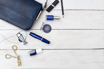 Female handbag of dark blue color and cosmetics on a wooden background. Flat lay