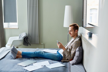 Profile view of smiling young freelancer texting with his colleague on smartphone while sitting on cozy bed, interior of modern studio apartment on background
