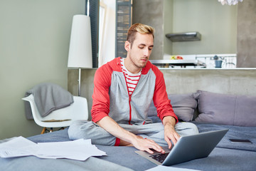 Concentrated young financial manager wearing sports suit preparing annual accounts on laptop while sitting on cozy bed covered with documents, interior of modern studio apartment on background