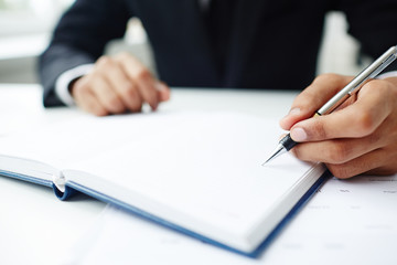 Close-up shot of unrecognizable entrepreneur wearing suit sitting at office desk and taking necessary notes while preparing for important business meeting
