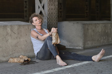a punk woman under a bridge with bottles of alcohol nearby and a bottle in a brown paper bag in her hand