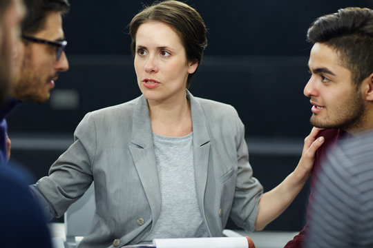 Experienced psychologist putting her hands on shoulders of two rivals during session