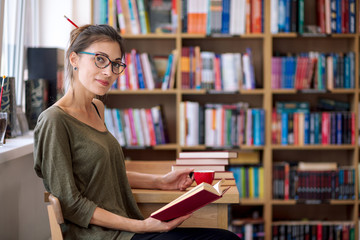 Woman with glasses reading a book with a cup of coffee