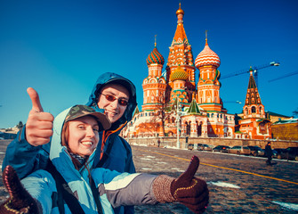 Happy tourists sightseeing city with fingers up next to Saint Basil's Cathedral. Red Square, Moscow, Russia. Holiday, travel, recreation. Winter season, bright colors, clear blue sky