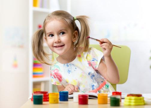Cute little girl painting in kindergarten