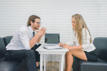 Professional businessman and businesswoman discussing together in the office, businesswoman signing on document