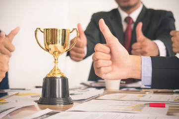 Businessman with colleagues achieve target and successful showing award trophy and thumb up