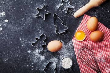 Cookies cutters, flour, rolling pin, eggs and whisk on kitchen table top view. Christmas baking background.