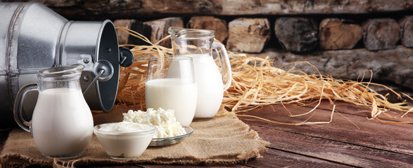 Photo sur Toile Produit laitier milk products. tasty healthy dairy products on a table on. sour cream in a bowl, cottage cheese bowl, cream in a a bank and milk jar, glass bottle and in a glass
