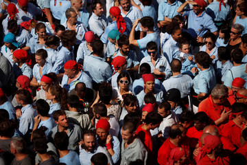 """A woman in sun glasses stands between members of """"castellers"""" during the festival of the patron saint of Barcelona """"The Virgin of Mercy"""" in Barcelona"""