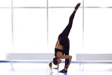 Young attractive woman doing exercises near window