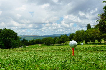close up of white golf ball on orange tee on green grass with blue sky and cloud. copy space for your text.